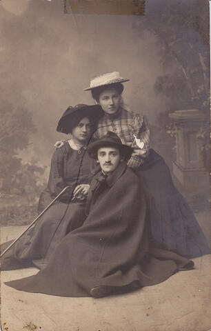 Yosef in a cape with two women