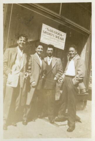 Four boys in front of a shop