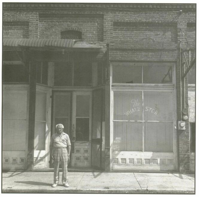 Aaron Kline in front of The Whale Store, Alligator. High-waisted pants-wearing elderly gent in front of a brick-facade store