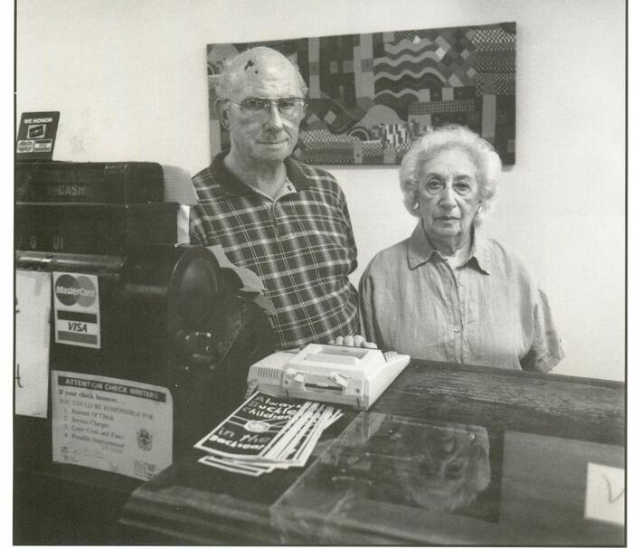 Melvin and Maureen Lipnick in Weinberg's, a children's store, Indianola. Elderly couple in front of a counter.