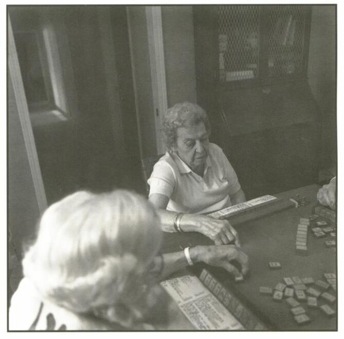 Elderly women playing mahjongg in a room. Juliet Kossman playing mahjongg at her home, Cleveland.