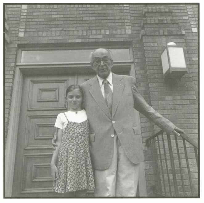 Rabbi Moses Landau and Melissa Chiz in front of the Adath Israel Temple, Cleveland, Mississippi. Elderly gentleman in suit, girl in dress, brick-facade synagogue.