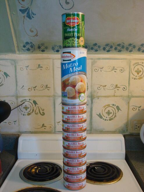 Cans of salmon and peas and a container of matzoh meal stacked up