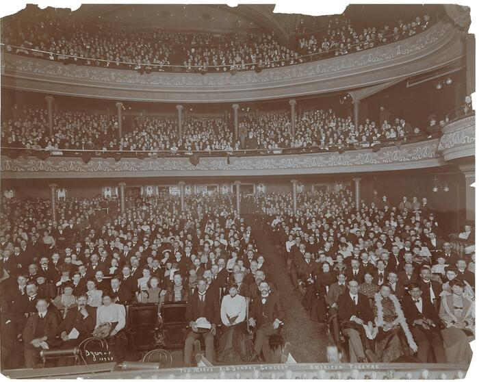 Sepia image of a large audience in the American Theatre, ca. 1902, all facing the camera.