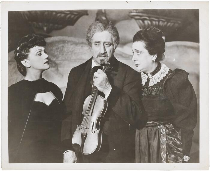 "A photo of the Yiddish actors Luba Kadison, Maurice Schwartz, and Berta Gersten in the play ""The Three Gifts,"" 1945, Schwartz holding a violin."