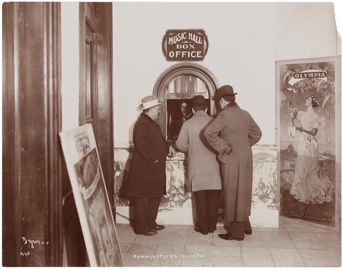 Three men standing at the box office of the Olympia Theatre, 1895, with a billboard featuring Yvette Luilbers visible.