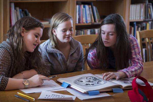 Three students sitting at a table discussing an illustrated Yiddish book.