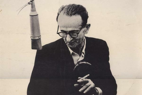 A photograph of Yiddish poet Itzik Manger in a recording studio preparing to read from his poems
