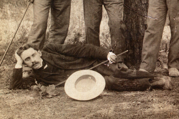Hersh David Nomberg reclines on the grass while posing for the camera with his friends